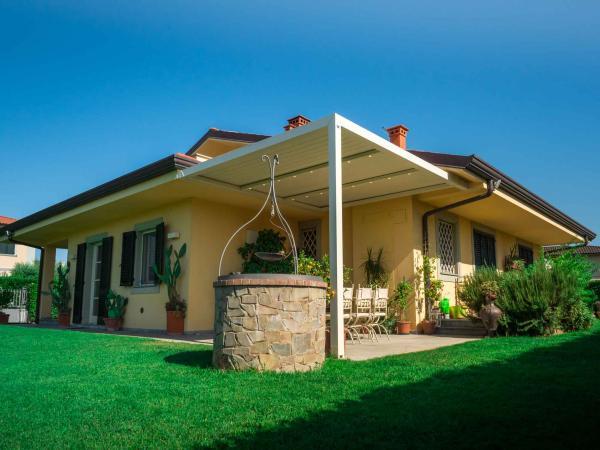 Pergola bioclimatica KEDRY PLUS A: struttura ombreggiante in alluminio con tetto a lame orientabili, in versione addossata con fissaggio a parete e pilastri di sostegno. Si adatta facilmente ad ogni contesto architettonico.